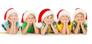 Group of happy Christmas kids in Santa hat lying down. White bac