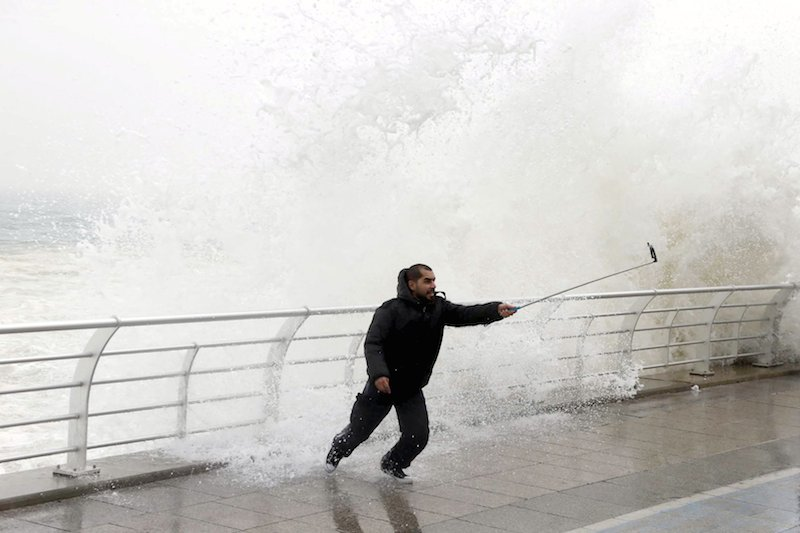 A man takes a selfie by a crashing wave on Beirut's Corniche, a seaside promenade, as high winds sweep through Lebanon during a storm in this February 11, 2015 file photo. The act of taking a picture of oneself with a mobile phone, placing the subject center-stage, has exploded in popularity in recent years. But the selfie has also inspired a spate of risk taking and offensive public behavior, pushing the boundaries of safety and decorum, whether by dangling from a skyscraper or posing with live explosives. Several governments and regulatory bodies have now begun treating the selfie as a serious threat to public safety, leading them to launch public education campaigns reminiscent of those against smoking and binge drinking. To match story LIFE-SELFIES/ REUTERS/Mohamed Azakir/Files