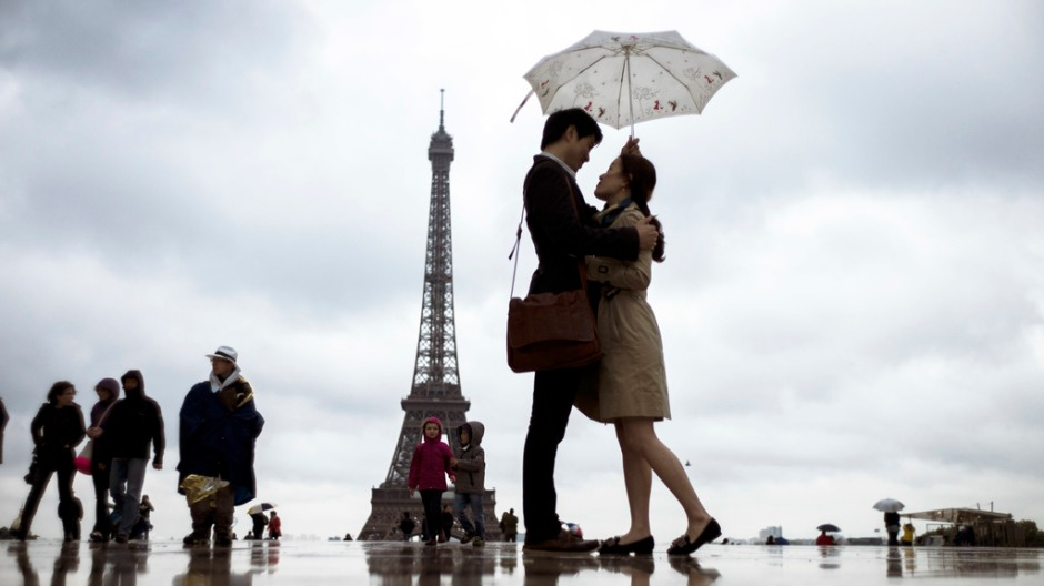 People gather on the Trocadero Square in front of the Eiffel Tower on a rainy day, on May 20, 2013, in Paris. AFP PHOTO / FRED DUFOUR        (Photo credit should read FRED DUFOUR/AFP/Getty Images)